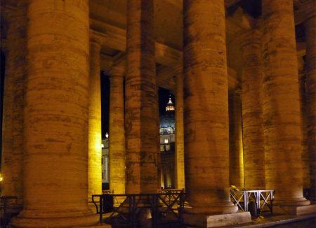 Blick durch die Säulenzeilen am Petersplatz auf den Petersdom (Italien).